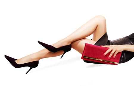 セクシーな黒のハイヒールを履いた美しい脚。赤い財布を持つ手。