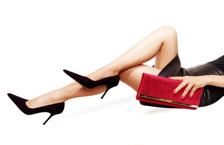 female hand: Beautiful legs wearing sexy black high heels. hand holding a red purse.