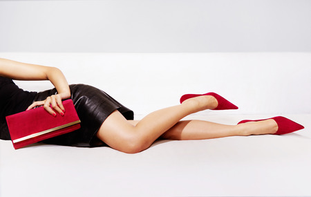woman red dress: Beautiful legs woman with party bag and sexy dress laying on the couch. Stock Photo