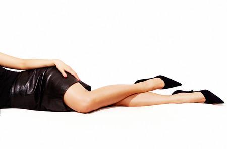 falda corta: Piernas de la mujer hermosa con falda de cuero negro acostado en la cama.