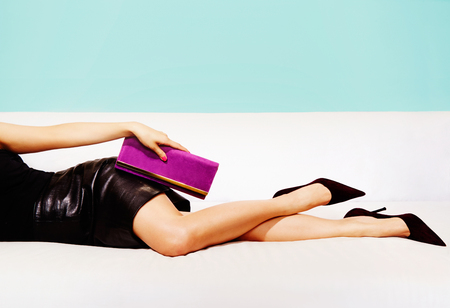 body bag: Beautiful legs woman with party bag and sexy dress laying on the couch. Stock Photo