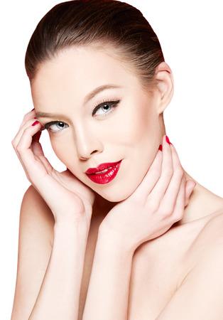 美しい女性は、彼女の肌に触れます。白で隔離。赤い口紅。