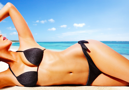 해변에 검은 비키니 입은 여자. 아름다운 무두질 한 피부. 스톡 콘텐츠