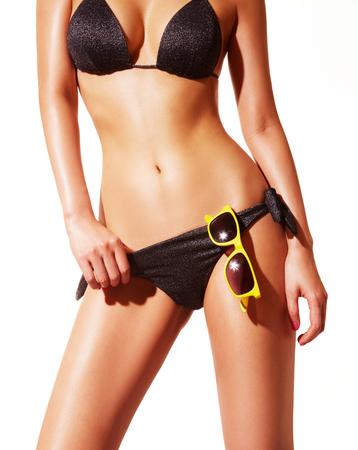 traje de bano: Cuerpo de la mujer hermosa con bikini negro y gafas de sol. Aislado en blanco ... Perfecto piel brillante para el verano.