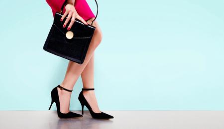 moda Mulher com saco bonito bolsa preta mão com sapatos de salto alto. cópia espaço no fundo azul claro. Isolado.