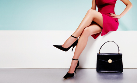 tacones rojos: Hermosa mujer piernas con un vestido rojo con bolso de mano bolso negro con zapatos de tacones altos sentado en el banquillo blanco. con copyspace.