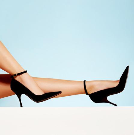 美脚にハイヒールが分離された黒の光青い背景。コピー スペース。 写真素材