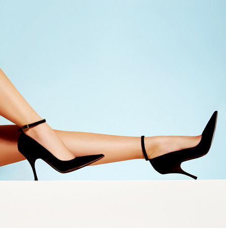 Beautiful legs with black high heels isolated on light blue background. with copy space.