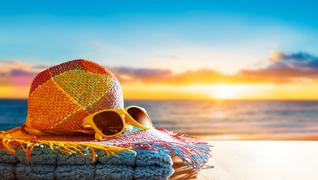 Letní dovolená na pláži. Barevný slaměný klobouk, žluté sluneční brýle a ručník na dřevěném stole. Kopírovat prostor pro text na stole a oblohu.