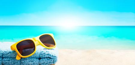 ビーチの砂の上の黄色いサングラスをかけた夏バカンス画像。海からの日差し。