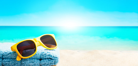 Summer vacation image with yellow sunglasses on the beach sand. Sunlight from the ocean. Imagens