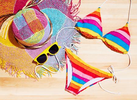 夏のカラフルなビキニ、麦藁帽子とサングラスの木のテーブル。休暇ファッションとショッピングのイメージ。