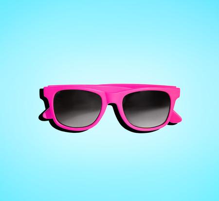 明るい水色の青い背景に分離されたピンクのサングラス。夏の休暇のファッションのイメージです。