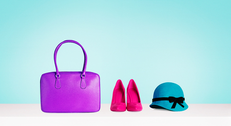 Woman colorful accessories isolated on aqua blue background. Purple bag, red heels shoes and green hat. Imagens