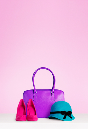 女性ファッション ・ アクセサリーは、コピー領域との分離のピンクの背景を設定します。紫手バッグ、赤いハイヒール、エレガントな緑の帽子フェ