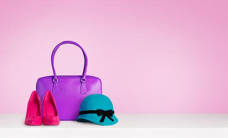 moda: Kolorowe akcesoria mody kobieta na stole samodzielnie na różowy. Czerwone buty i niebieski kapelusz zielony i fioletowy skórzany torba. Zdjęcie Seryjne