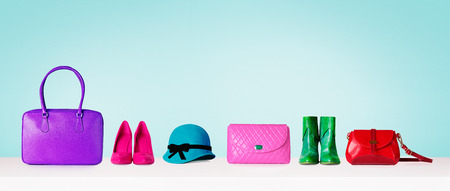 Colorful hand bags, shoes, and hat isolated on light blue background. Woman fashion accessories item. Shopping image. 스톡 콘텐츠