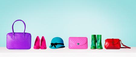 다채로운 손 가방, 신발 및 밝은 파란색 배경에 고립 된 모자. 여자 패션 액세서리 항목입니다. 이미지를 쇼핑.
