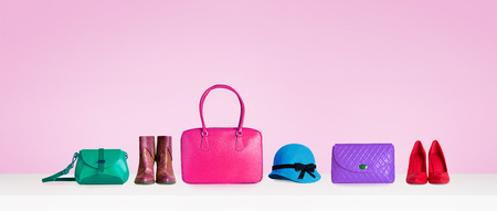 Colorful hand bags, shoes, and hat isolated on pink background. Woman fashion accessories item. Shopping image