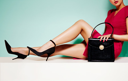Beautiful legs woman with black high heels shoes and handbag purse... sitting on white table. Isolated on the light green background.