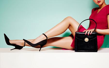 piernas con tacones: Hermosa mujer piernas con zapatos de tacones altos negros y monedero ... sentado en la mesa blanca. Aislado en el fondo verde claro. Foto de archivo