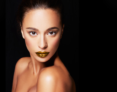 Beautiful woman with bronze skin and gold lipstick lips isolated on black background. Perfect skin texture cosmetic makeup image. with copyspace