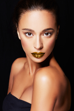 Beautiful woman with bronze skin and gold lipstick lips isolated on black background. Perfect skin texture cosmetic makeup image. Imagens