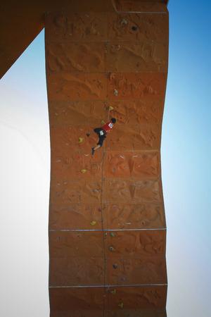 Man on artificial exercise climbing wall photo