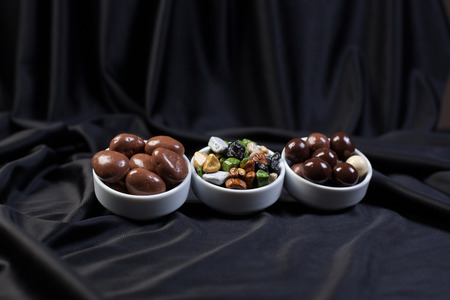 Dark brown dragee, chocolate covered nuts, background photo