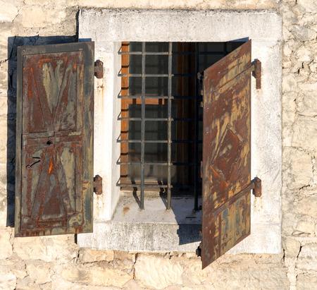 security shutters: Opened rusty metal window shutters, security element