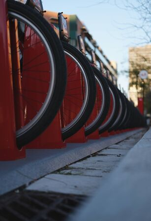 Vertical photo of a red bicycle parking in an autumn city close up