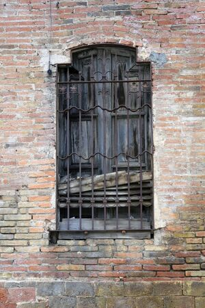 Horizontal photo of an old window on a background of a brick wall with steel bars in an abandoned house