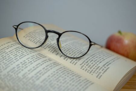 Horizontal photo in retro style glasses, red apple and old open book on a wooden table. Soft focus. Close up