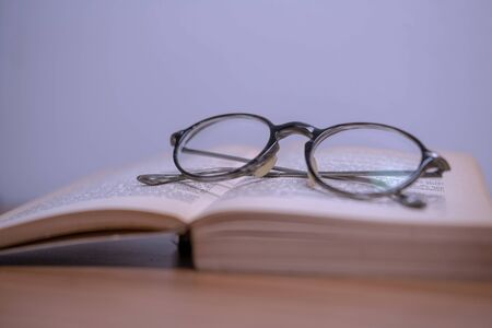 Horizontal photography in vintage style glasses and an old yellowed book on a wooden table