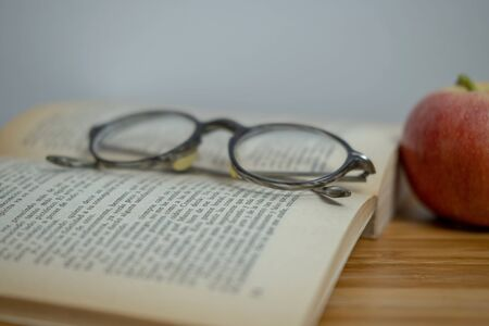 Horizontal photography in vintage style, round glasses, a red apple and an old yellowed opened book on a wooden table