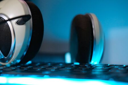 Headphones and computer keyboard backlit soft focus and close up horizontal photo