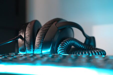 Headphones and computer keyboard with soft backlight blurred focus and close up horizontal photo