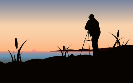 Vector illustration black silhouette of a photographer from the back standing on the seashore with grass and reeds photographing the setting sun with a tripod against the background of a yellow blue sky. Stock Photo