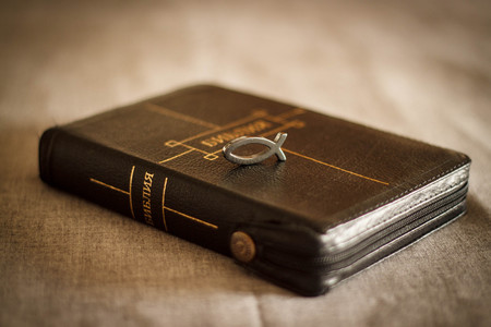 picture of a book Bible close-up in black leather binding with a zipper with a Christian pendant symbol fish on a gray background. Stock Photo
