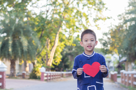 rea: Boy hold rea heart with bokeh from tree background