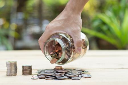 Hand holding savings glass and throw on wood