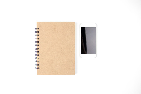 white sheet: Copy space brown of book and mobile top view angle, white isolated background