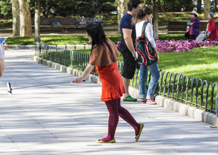 herself: Madrid, Spain - October 02, 2014: A Japanese woman tourist takes pictures of herself with her mobile phone Editorial