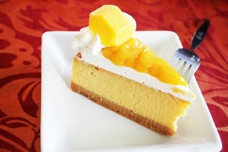 A delicious slide of mango cheese pie with fork photo