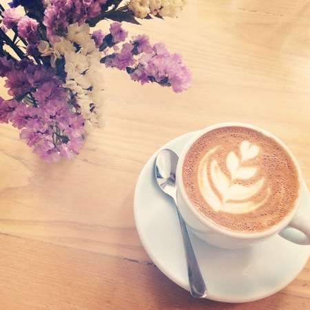 statics: A cup of latte on the table with statics flower with retro filter effect  Stock Photo