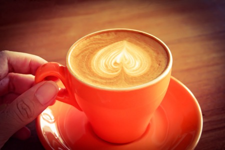 sip: Hand holding cup of latte or cappuccino already sip , retro vintage filter effect
