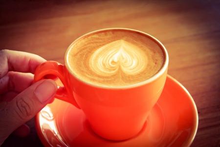 sorbo: Mano que sostiene la taza de caf� con leche o un capuchino ya sip, efecto retro filtro de la vendimia