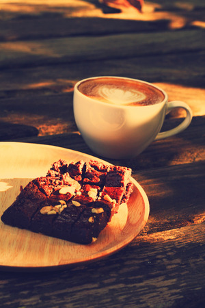 Cup of latte or cappuccino and brownie in retro filter effect  photo