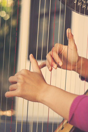 arpa: Primer plano de una mujer tocando el arpa, efecto de filtro retro