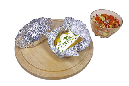 potato with curd and chive in foil on wooden plate and cup of vegetables photo